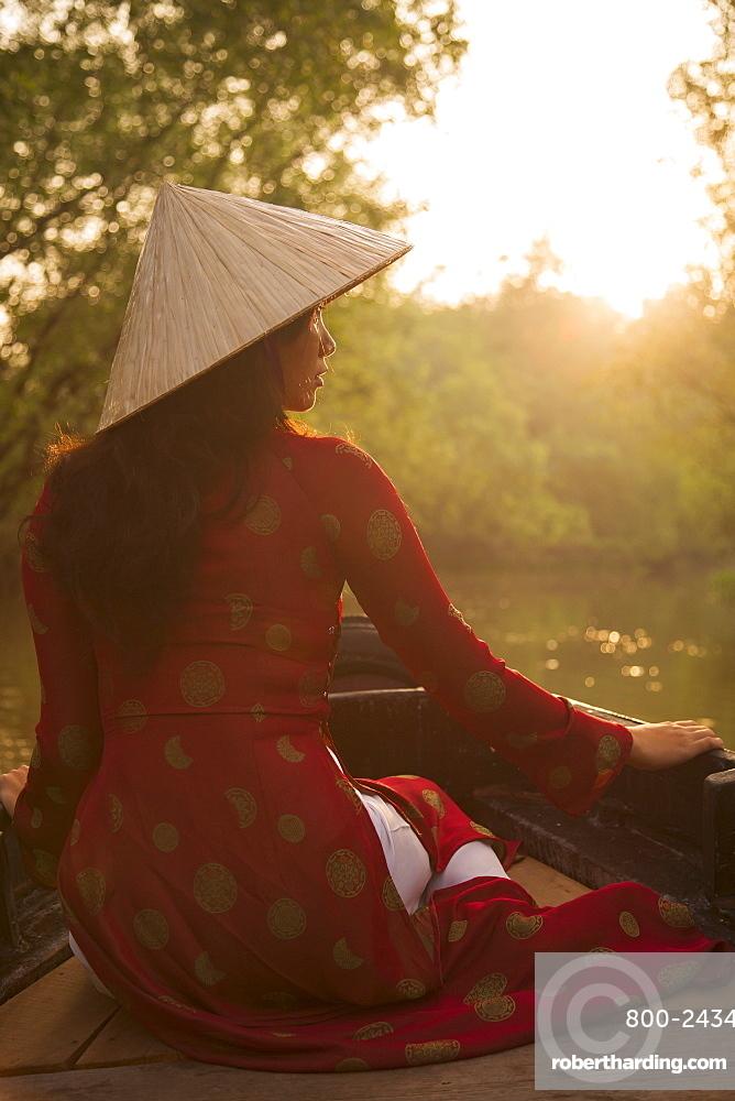 Woman wearing ao dai dress in boat, Can Tho, Mekong Delta, Vietnam, Indochina, Southeast Asia, Asia