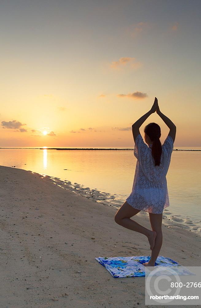 Woman practising yoga at sunrise, Rasdhoo Island, Northern Ari Atoll, Maldives, Indian Ocean, Asia