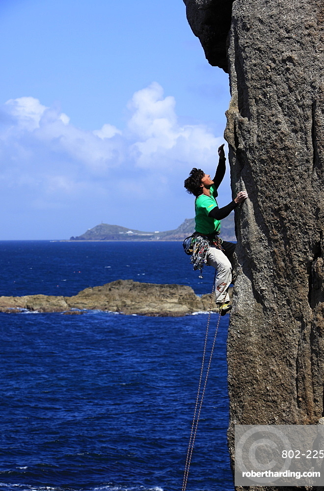 A climber scales cliffs at Sennen Cove, Cornwall, England, United Kingdom, Europe