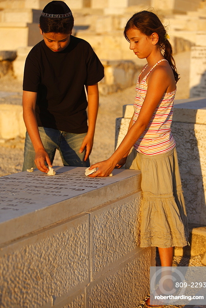 Brother and sister placing stones on a grave in the Mount of Olives Jewish cemetery, Jerusalem, Israel, Middle East
