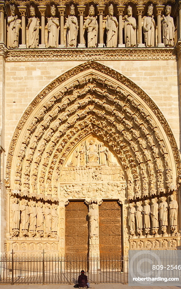 Woman praying in front of Last Judgment gate, west front, Notre Dame Cathedral, UNESCO World Heritage Site, Paris, France, Europe