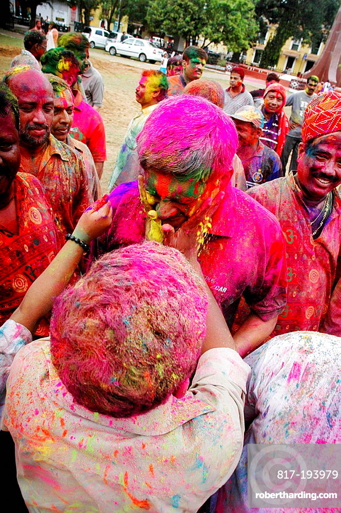 Panjim Goa, India, men putting colored powder on their faces during the Holi feast