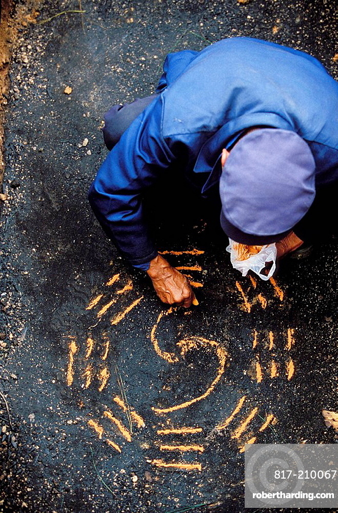 Feng shui expert tracing the bagwa, the 8 sacred trigrams, on the tombs ground, han funeral, pingtang, guizhou, China