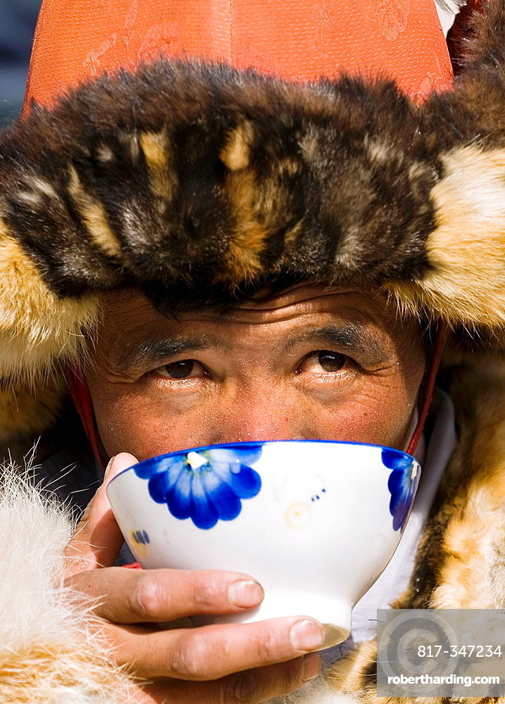 A Kazakh eagle hunter enjoys a hot cup of milk tea.