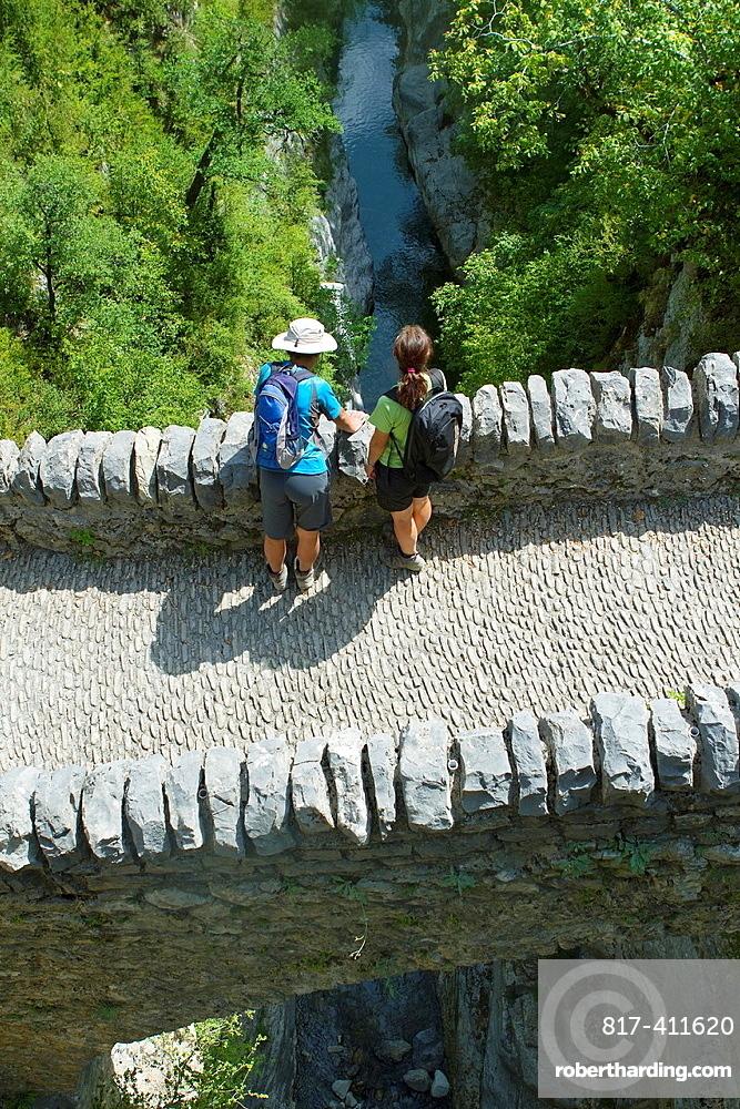 Hikers walking on San Urbez Bridge above Bellos river, in Anisclo Valley, canyon belonging to Ordesa y Monte Perdido National Park Pyrenees Fanlo Huesca province Aragon Spain