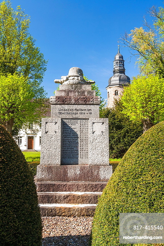 War memorial and the Church of St. Viti monastery in the background in Zeven, Lower Saxony, Germany, Europe