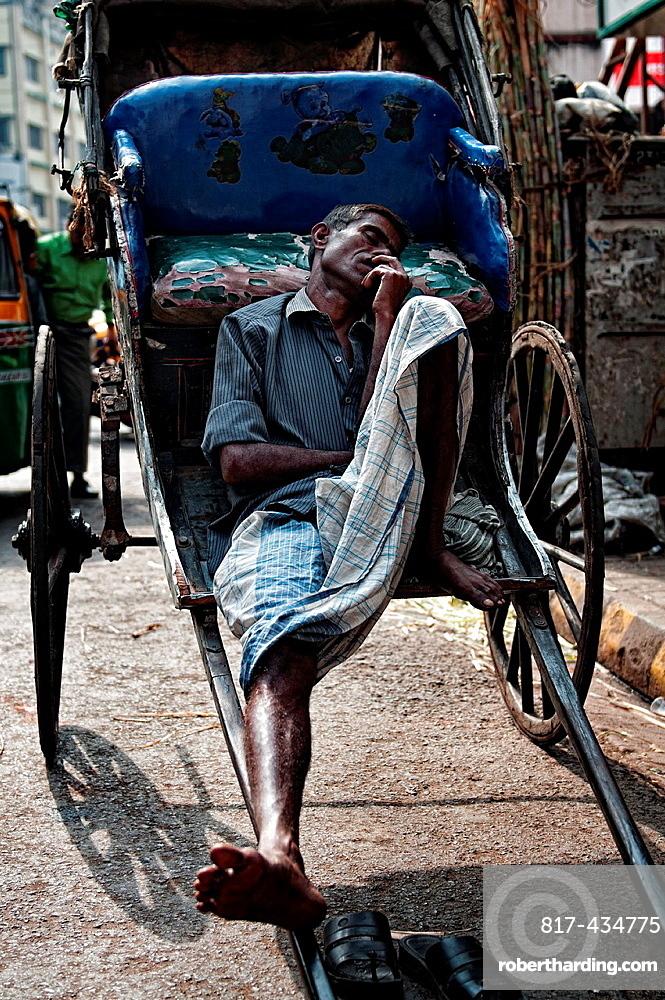 Rickshaw wallah sleeping in the streets of Calcutta, Kolkata, West Bengal, India