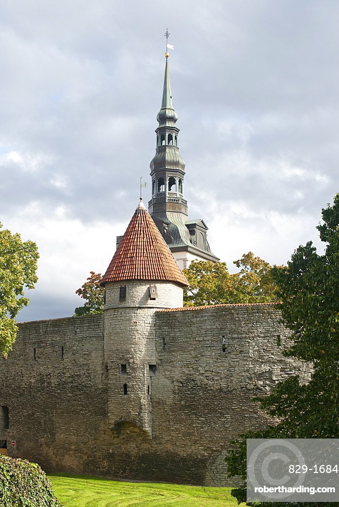 View of St. Nicholas' Church steeple and part of the wall of the old town in Tallinn, UNESCO World Heritage Site, Estonia, Baltic States, Europe