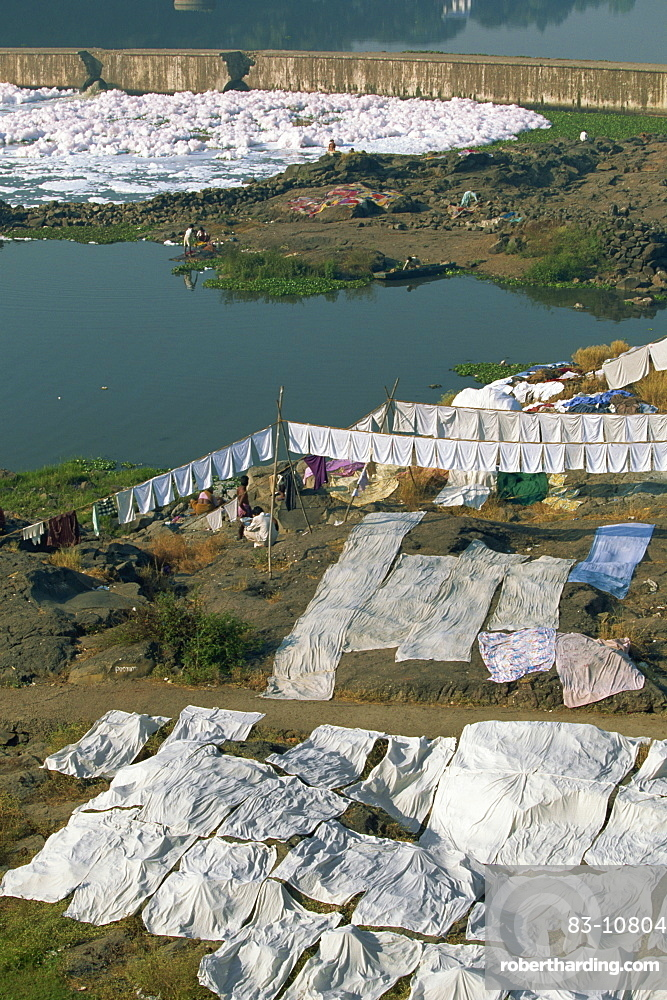 Laundry drying by the Mula River, with foam from detergent pollution beyond, Pune, Maharashtra state, India, Asia