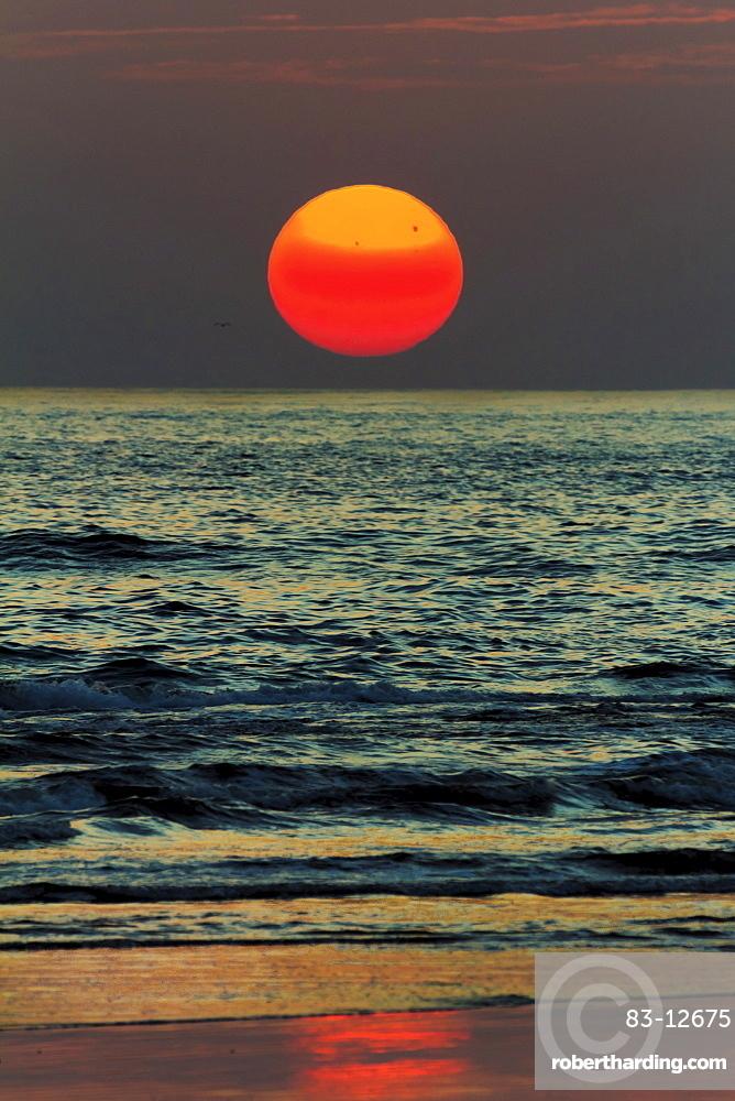 The sun setting off Playa Guiones surf beach, Nosara, Nicoya Peninsula, Guanacaste Province, Costa Rica, Central America