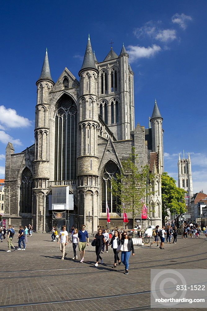 Young people enjoy summer sunshine in streets outside St. Nicholas' Church, city centre, Ghent, West Flanders, Belgium, Europe