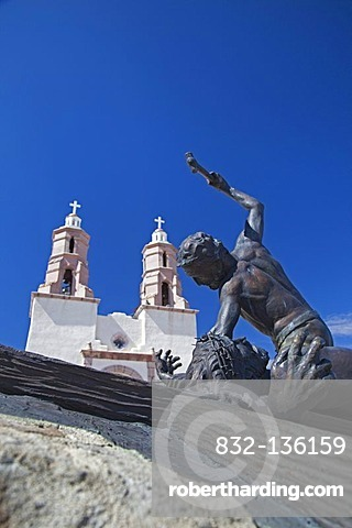 The Shrine of the Stations of the Cross, sculptures by artist Huberto Maestas, on a hill above town, the Chapel of All Saints at back, San Luis, Colorado, USA
