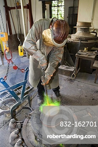 Bronze being heated in a melting pot on a gas stove in an art foundry