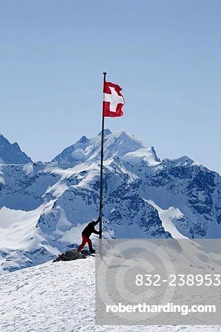 Swiss national flag and alpine sportspeople on the plateau Trais Fluors, St. Moritz, Oberengadin, Graubuenden, Switzerland