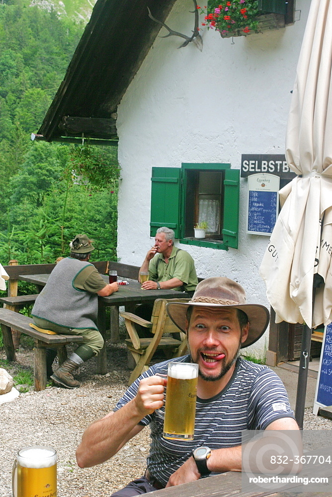 A man enjoys a cool beer at the Mairalp at the base of the mountain Traunstein Upper Austria