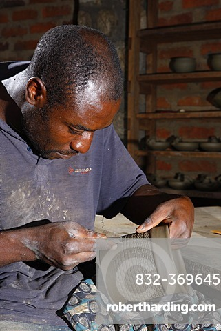 Man decorating a clay pot with ornaments, manufacture of pottery, Bamessing, Cameroon, Africa