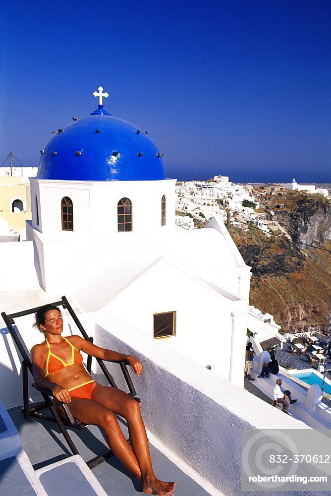 Woman lying on a deckchair on the terrace of a hotel near Thira, Santorini, Cyclades, Greece, Europe