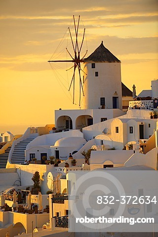 Windmills and town at sunset, Oia, Ia, Santorini, Cyclades Islands, Greece, Europe