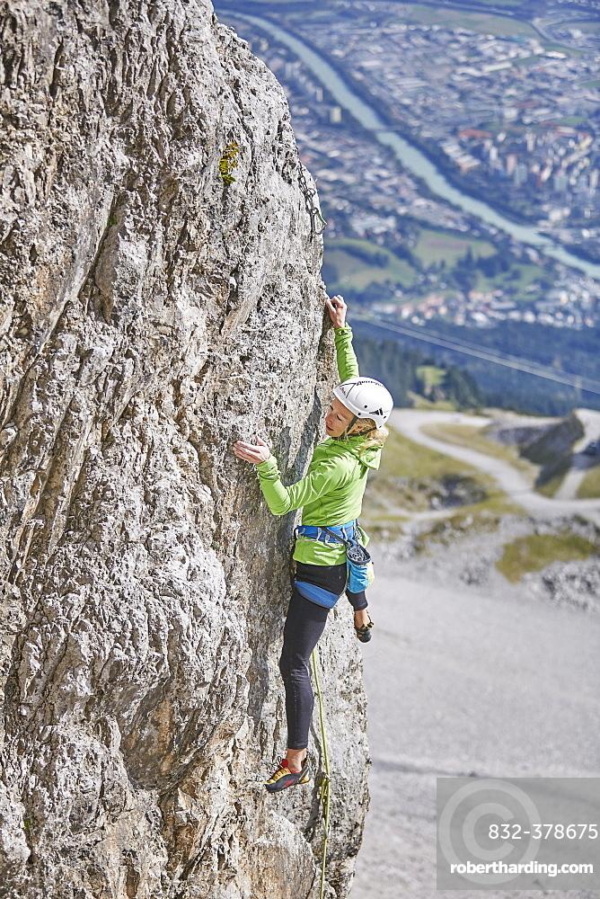 Climber with helmet climbing on a rock wall, behind Innsbruck, Northern Alps, Innsbruck, Tyrol, Austria, Europe