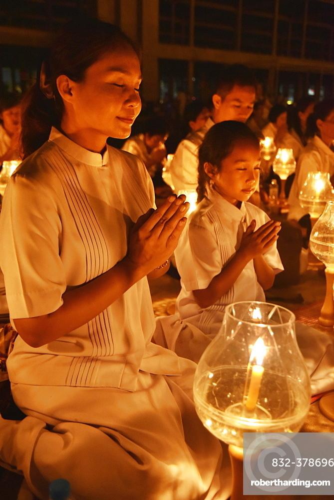 Young woman and child praying, candlelight, Wat Phra Dhammakaya temple, Bangkok, Thailand, Asia