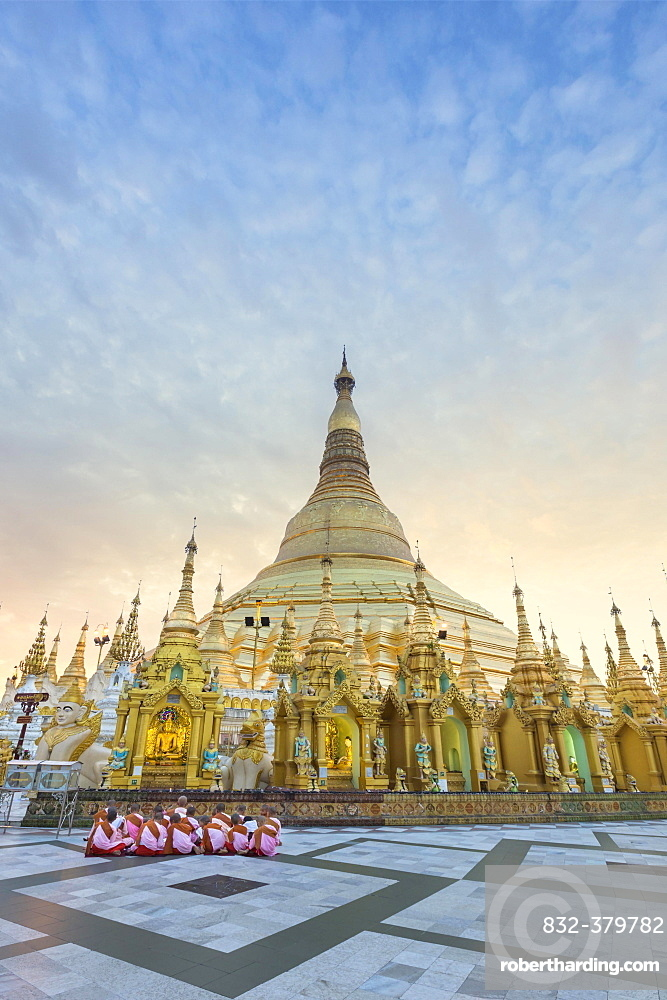 Nuns sitting in front of the Shwedagon pagoda, Shwedagon Paya, morning light, Yangon, Myanmar, Asia