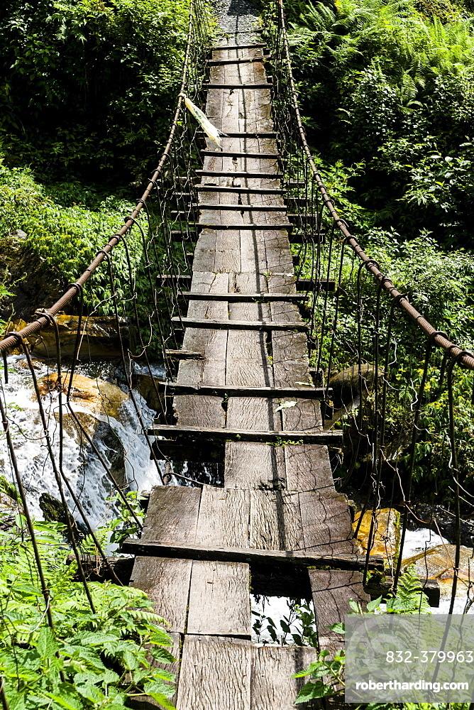 Old wooden suspension bridge across small river in Upper Modi Khola valley, Landruk, Kaski District, Nepal, Asia