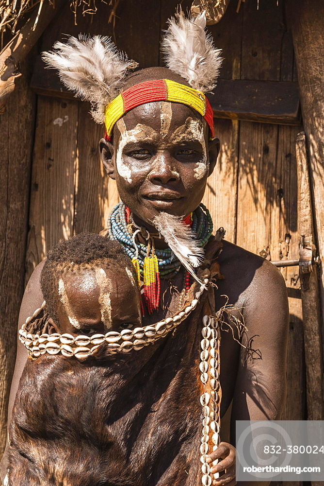 Young woman with toddler in traditional clothes made of goatskin, Karo tribe, Southern Nations Nationalities and Peoples' Region, Ethiopia, Africa