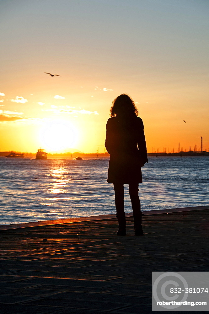 Woman watching the sunset on the Zattere promenade, Venice, Italy, Europe