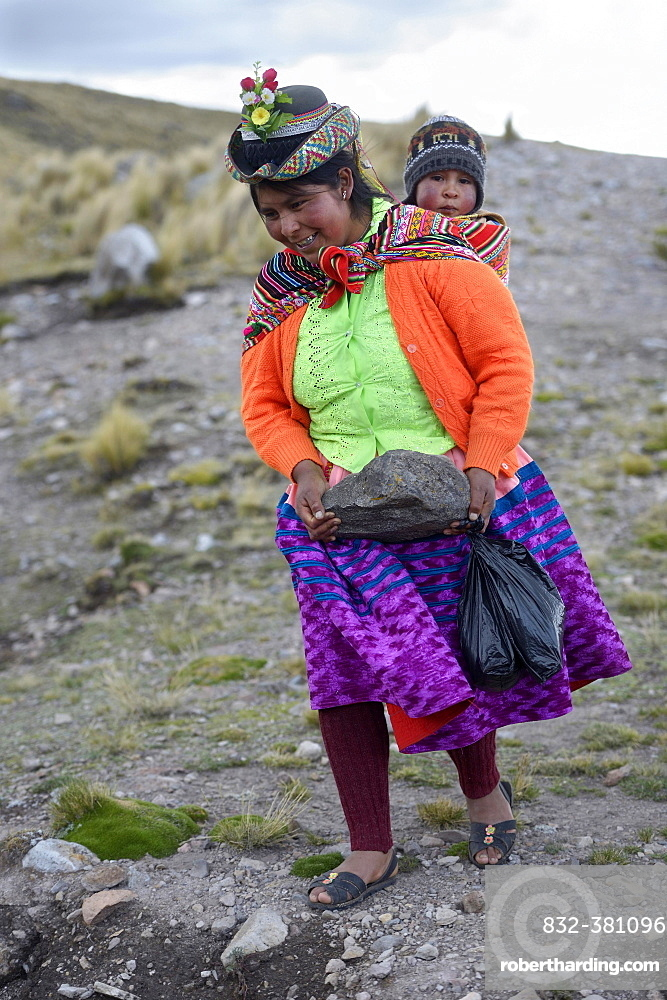 Young woman with child in a sling carrying a heavy stone to secure the shores of an artificial lake for irrigation, Quispillacta, Ayacucho, Peru, South America