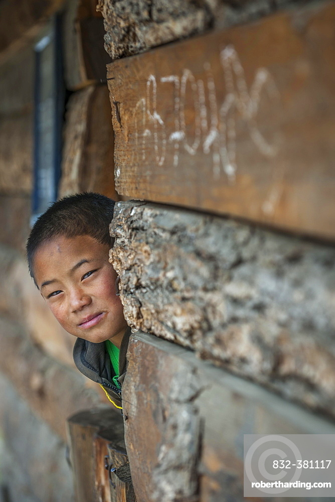 A boy looks out of a house, Wangue, Himalayas, Kingdom of Bhutan