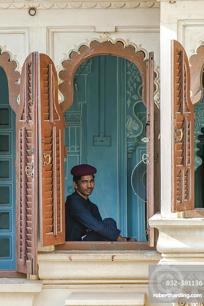 Museum guard sitting by the window in the City Palace of the Maharaja, Udaipur, Rajasthan, India, Asia