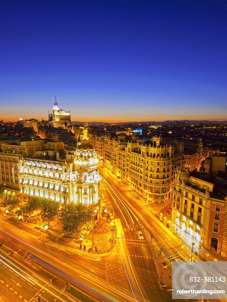 Elevated view over town with Metropolis Building, illuminated streets, at dusk, Madrid, Spain, Europe