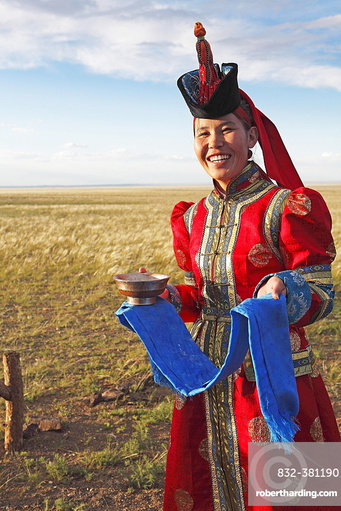 Woman in traditional dress with traditional welcome utensils, blue cloth and bowl of milk, Gobi desert, Sudwuste, Omnogovi Province, Mongolia, Asia