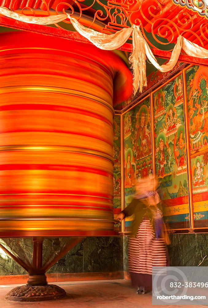 A female devotee spinning a large prayer wheel, Boudhanath, Kathmandu, Kathmandu District, Bagmati Zone, Nepal, Asia
