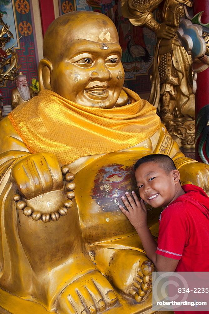 Young Boy with Buddha statue, Chinatown, Bangkok, Thailand, Southeast Asia, Asia
