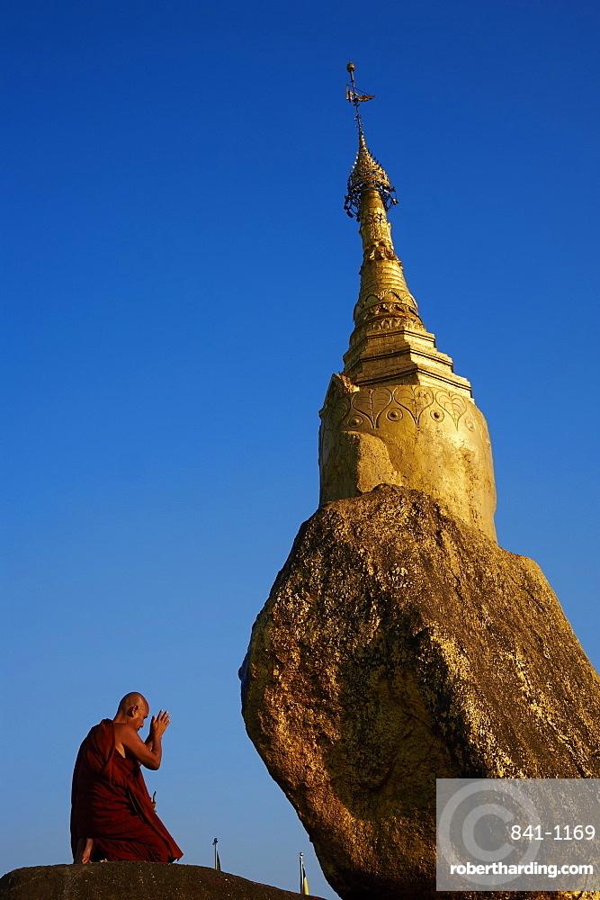 Buddhist monk praying at the Golden Rock of Nwa La Bo, Mawlamyine (Moulmein), Mon State, Myanmar (Burma), Asia