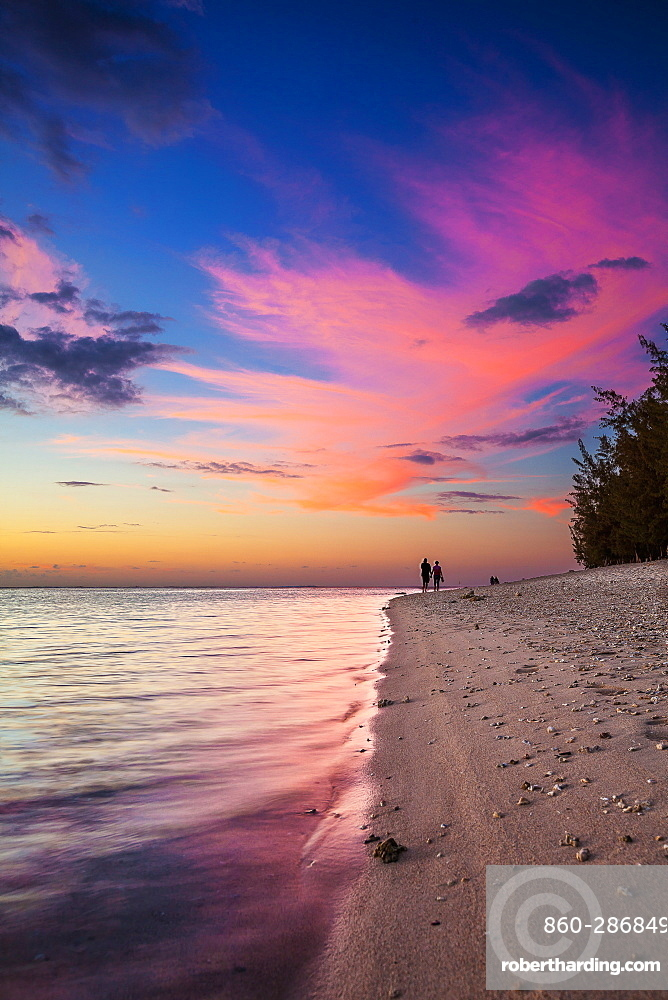 Couple walk at sunset on the beach of l'Ermitage, La Reunion Marine Nature Reserve, Indian Ocean