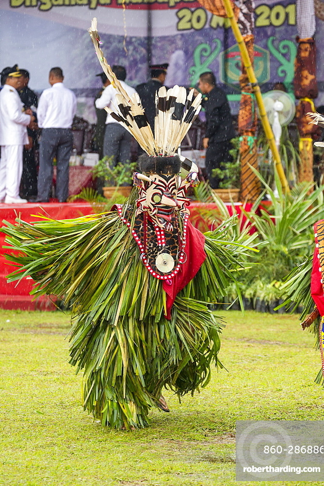 Masqked man wearing feather hornbill during Parade Hudoq