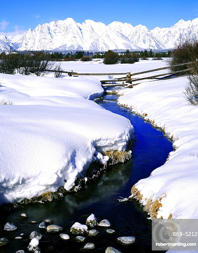 splitrail fence across a stream below the Teton Range in winter Grand Teton National Park Wyoming USA