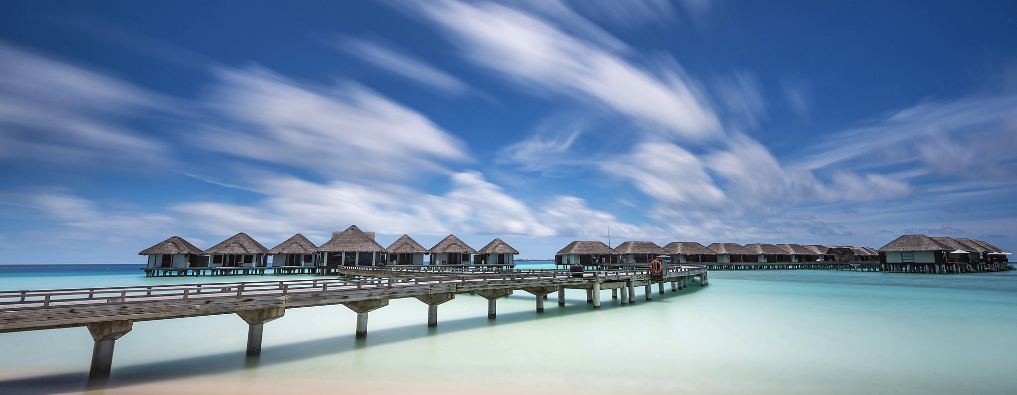 1174-4395 ( Mint Images ) - Huts along a walkway in clear ocean waters.